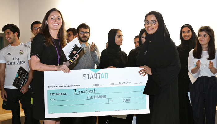 A girl in abaya is receiving a cash prize from StartAd