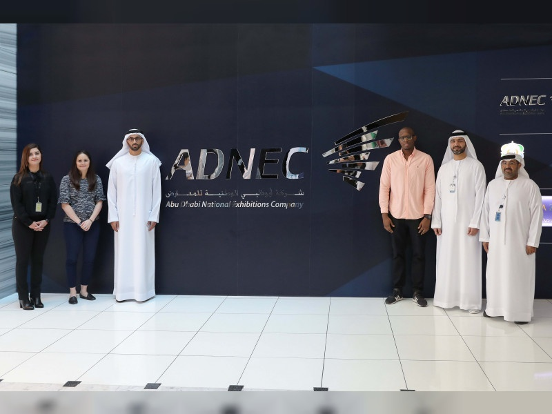 ADNEC logo on wall and three people on left of it and three on the right