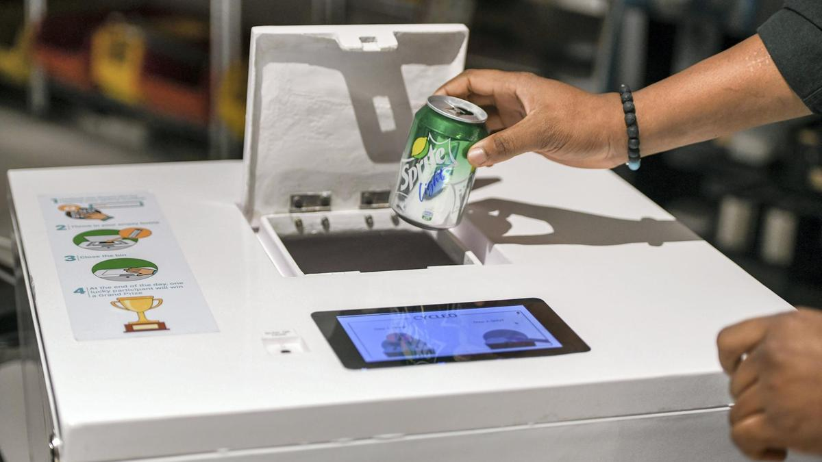 person throwing a sprite can in a recycling machine